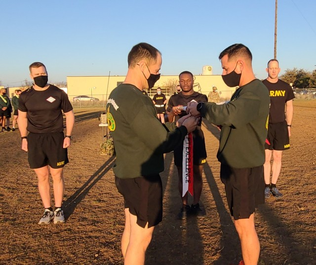 3rd Cavalry Regiment Commander, Col. Kevin Bradley and Command Sgt. Maj. Shade Munday present Eagle Troop, 2nd Squadron with the RCO PT Excellence Streamer following the Troops Rifles Challenge win. (U.S. Army photo by Maj. Marion Jo Nederhoed)