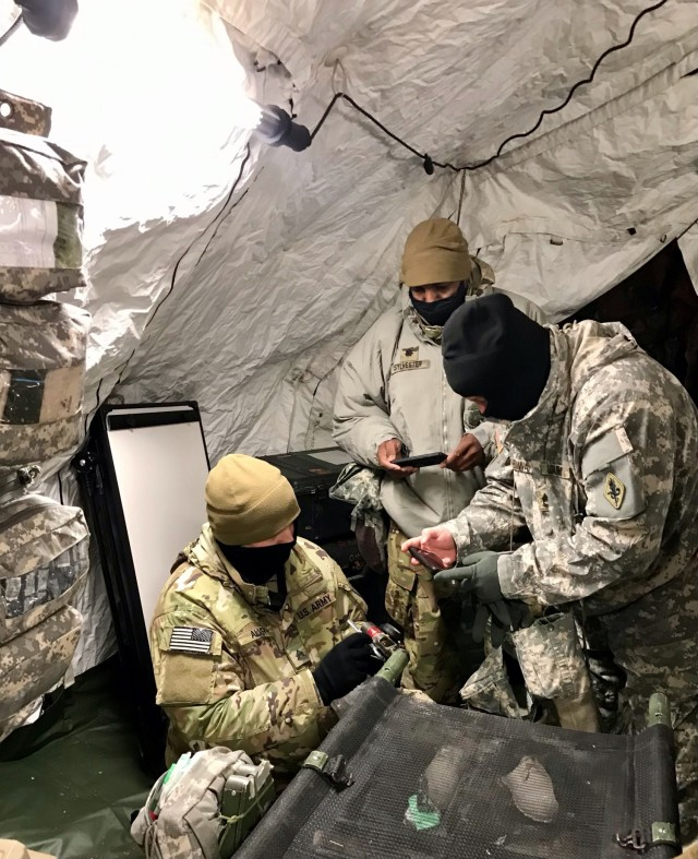 (L-R): A medic from 4th Brigade, 25th Infantry Division, Lt. Col. Cleve Sylvester, and Master Sgt. David Edwards, assess CLVIII at Role 1, in support of Arctic Warrior 2021 at Fort Greely, Alaska, February 6-12, 2021.