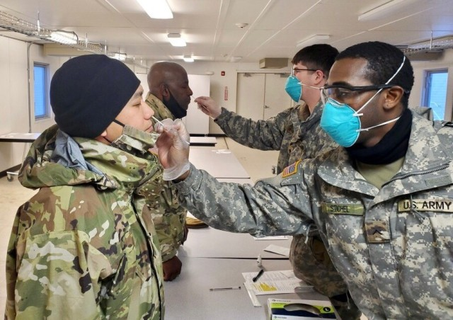 Col. Joselito Lim (left) and Lt. Col. Cleve Sylvester (middle), are screened by medics from 1/25 ID as part of daily COVID-19 screening prior to start of Arctic Warrior in Fort Greely, Alaska, February 6-12, 2021.
