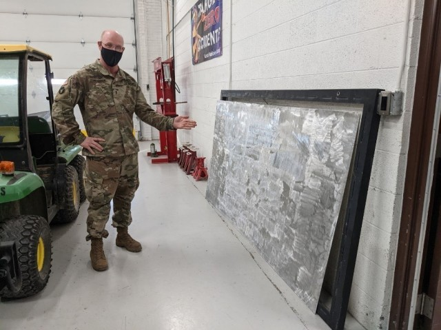 HAYS, Kan. – Chief Warrant Officer 3 Michael Schmidtberger, Field Maintenance Shop 1 shop foreman, shows off a work in progress for their outdoor shop sign Jan. 28, 2021. Part of their new sign is being finished in Salina as the former one became sun-bleached and faded over the years. The FMS 1 took first place at the National Guard Bureau for the annual Army Award for Maintenance Excellence in December 2020 in the Tables of Distribution and Allowances category.