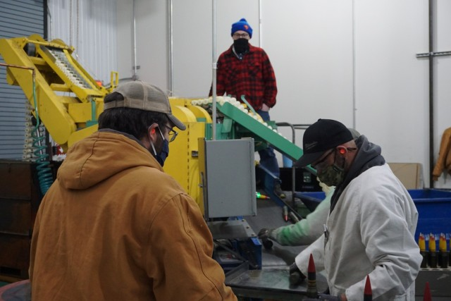 Tooele Army Depot mechanical engineer, Courtney Anderson (front left), watches as ammunition worker, Jeff Medrano, puts 30mm rounds into the Super Pull Apart Machine (SPAM).
