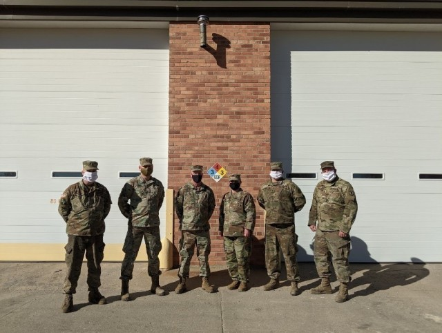HAYS, Kan. – The Field Maintenance Shop 1 team takes a moment for a group photo outside of their maintenance bays Jan. 28, 2021. FMS 1 took first place at the National Guard Bureau for the annual Army Award for Maintenance Excellence in December 2020 in the Tables of Distribution and Allowances category. Pictured from left to right: Sgt. 1st Class Lyndon Ellis, Sgt. 1st Class Lance Jones, Chief Warrant Officer 3 Michael Schmidtberger, Sgt. Brandi Brooks, Spc. Theo Stone and Staff Sgt. Dennis Dinkel. Not present are Warrant Officer 1 Michael Murphy, Staff Sgt. Luke Pechanec, Sgt. Blake Slife and Spc. Jake Romey.
