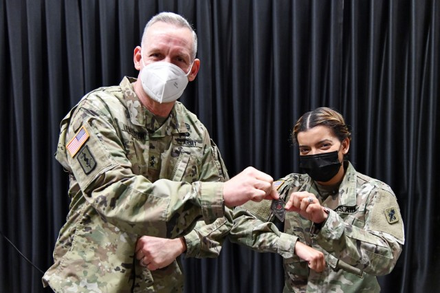 Maj. Gen. Dennis P. LeMaster, Commanding General MEDCoE, presents a commander's coin to Capt. Amaya Vargas, Commander, Bravo Company, 188th Medical Battalion for organizing and moderating the Women's History Month panel discussion.