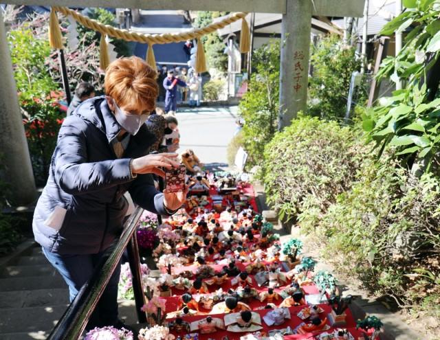 "Suzanne Ohsiek, participating in a U.S. Army Garrison Japan Army Community Service walking tour, takes photos of ""Hinamatsuri"" dolls at the Zama Shrine, Zama, Japan, March 3."
