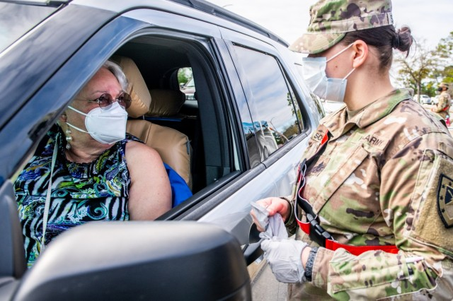 Carmen Colon listens to Staff Sgt. Samantha Schwigen, a combat medic with 316th Cavalry Brigade, as she explains the vaccine procedure.