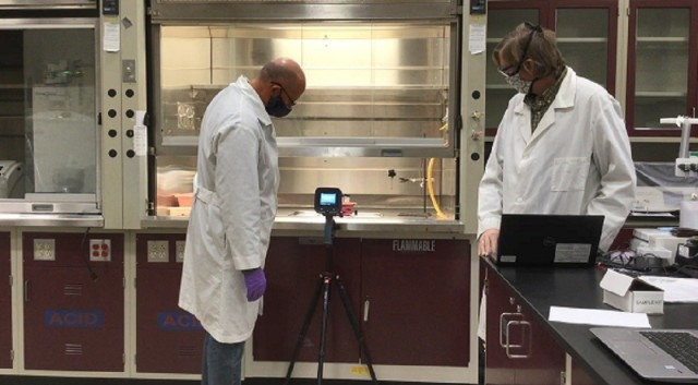 Electrical engineer Dr. Phillip Wilcox and research chemist Dr. Jason Guicheteau test the capabilities of a handheld standoff chemical detection device in a DEVCOM CBC laboratory.
