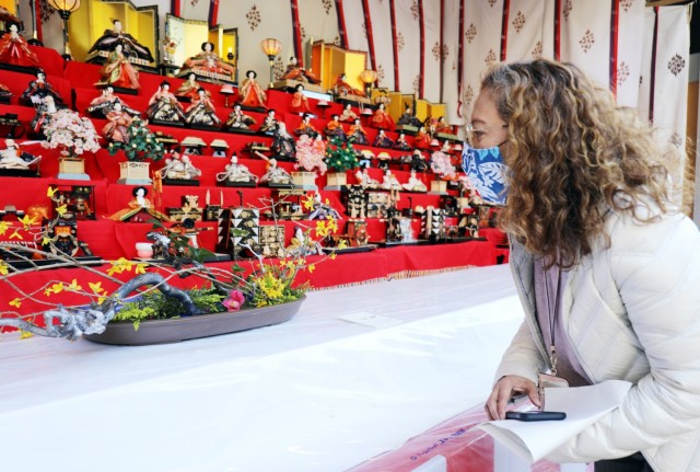 "Marissa Ayag-Garcia, participating in a U.S. Army Garrison Japan Army Community Service walking tour, observes ""Hinamatsuri' dolls and a work of ""ikebana,"" the Japanese art of flower arranging, at the Zama Shrine, Zama, Japan, March 3."