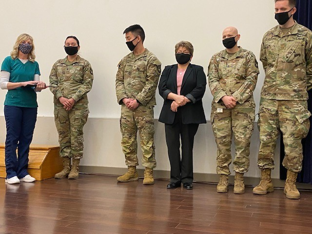Brig. Gen. James Bienlien, the Natick Soldier Systems Center senior commander, presented coins to key medical staff during an impromptu ceremony Feb. 24 at Hunter Auditorium. Vicki Juncker (far left) earned an on-the-spot award for her work on the front line of the team. (USAG Natick photo by Vannessa Josey, USAG Natick Public Affairs)