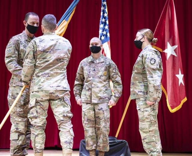 Lt. Gen. Daniel L. Karbler, Commander, U.S. Army Space and Missile Defense Command, passes the 1st Space Brigade guidon to incoming brigade commander Col. Donald K. Brooks during an assumption of command ceremony held at Fort Carson, CO March 5th, 2021.