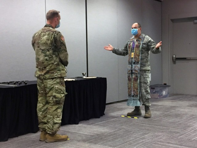 Air Force Chaplain (Lt. Col.) Jake Marvel, with the New York Air National Guard, gives Holy Communion to a U.S. Army Soldier at New York City's Jacob K. Javits Convention Center, on Easter Sunday. Marvel has been mobilized to the alternate care facility as part of a Religious Support Team in response to COVID-19. (U.S. Air National Guard Photo by Staff Sgt. Nicholas Mancuso)