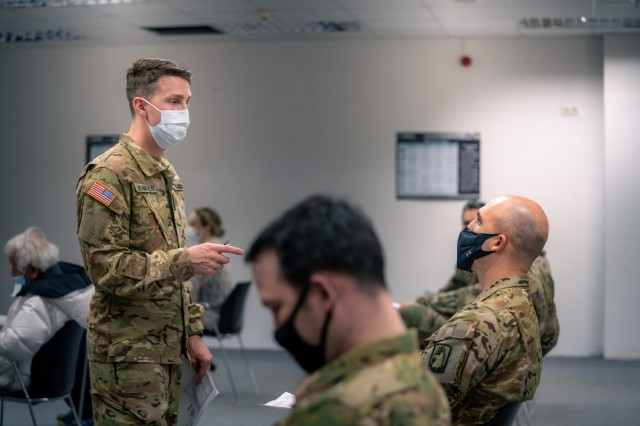 U.S. Army Capt. (Dr.) Charles Behnfield, flight surgeon for the 1st Battalion, 214th Aviation Regiment, 12th Combat Aviation Brigade, goes over questions and instructions with Soldiers prior to receiving their second COVID vaccine on Feb. 24, 2021, in Wiesbaden, Germany.