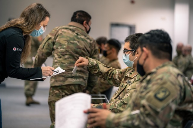 A U.S. Army Soldiers from 1st Battalion, 214th Aviation Regiment, 12th Combat Aviation Brigade, go through questions and instructions prior to receiving their second COVID vaccine on Feb. 24, 2021, in Wiesbaden, Germany. (U.S. Army photo by Maj. Robert Fellingham)