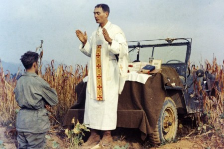 Father Emil Kapaun celebrates Mass using the hood of his jeep as an altar, as his assistant, Patrick J. Schuler, kneels in prayer in Korea on Oct. 7, 1950, less than a month before Kapaun was taken prisoner. Kapaun died in a prisoner of war camp on May 23, 1951.