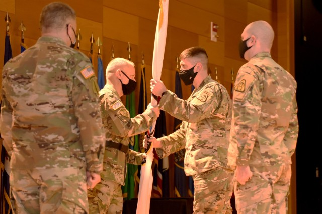Brig. Gen. Rob Collins, PEO C3T, passes the charter for Project Manager Mission Command to Col. Mike Williams during a Change of Charter ceremony on March 2.