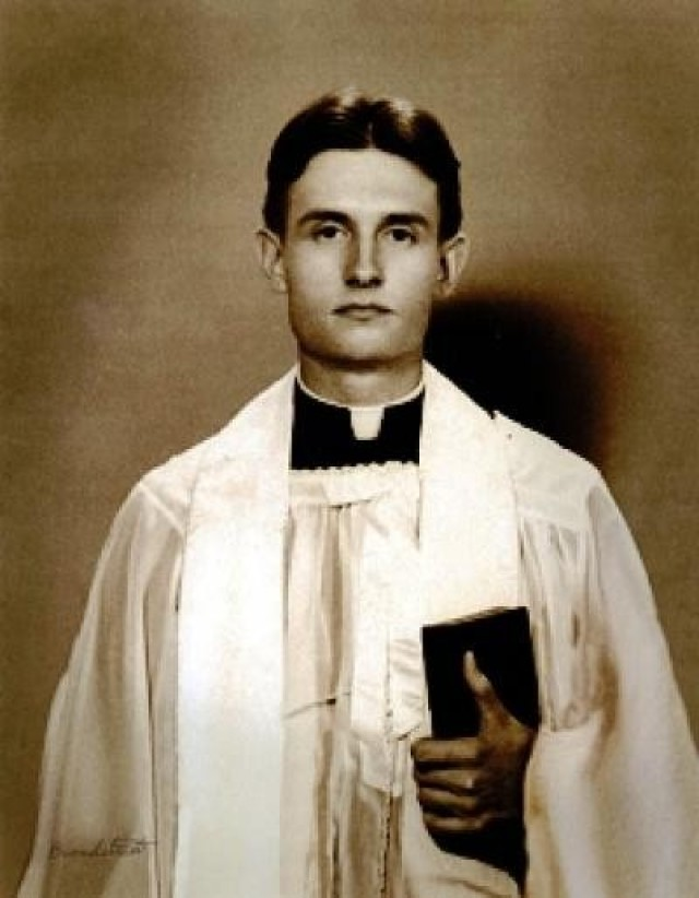 Chaplain (Capt.) Emil J. Kapaun poses for a photo in liturgical dress, holding a bible.