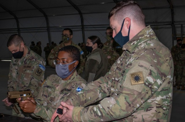 Sgt. Abraham Boxx, a critical care flight paramedic, teaches Pfc. Mariyah Berry, an automated logistical specialist, both assigned to Regional Command-East, Kosovo Force, how to handle a Sig Sauer M17 pistol during an aviation stand down at Camp Bondsteel, Kosovo, on March 6, 2021. Hands-on instruction allows Soldiers to gain familiarity with weapon systems they haven't used before in a safe environment. (U.S. Army National Guard photo by Sgt. Jonathan Perdelwitz)