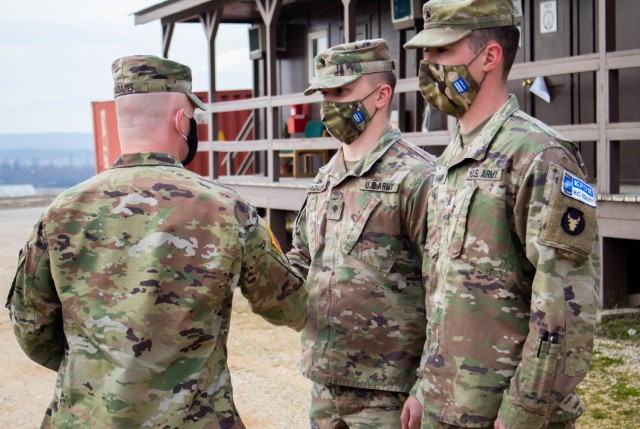 Col. Derek Adams, commander of Regional Command-East, Kosovo Force, presents a coin to Spc. Cole Magnuson during a recognition ceremony at Camp Bondsteel, Kosovo, on March 8, 2021. Magnuson, along with Sgt. Spenser Sharp, demonstrated their dedication to selfless service by going out of the way to aid civilians during an emergency. (U.S. Army National Guard photo by Sgt. Jonathan Perdelwitz)