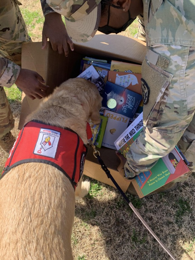 Shiloh, Chief Cheer Officer, and an honorary Better Opportunities for Single Service Members honorary member, inspects donated books, March 5, 2021, Dallas, Texas. The books donated are scheduled to be given to the children who attend the Ronald McDonald House. (U.S. Army courtesy photo)