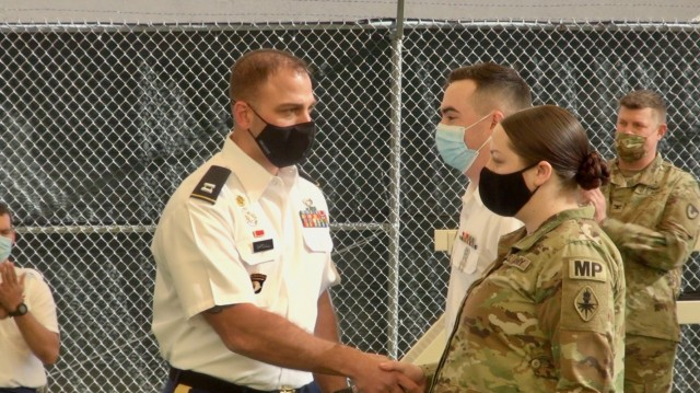 Capt. Anthony Gardull, Commander, 483rd Military Working Dog, and 18th Military Police Detachments presents challenge coins to Soldiers during a Buffalo Soldier Day's event at Fort Huachuca, Ariz.