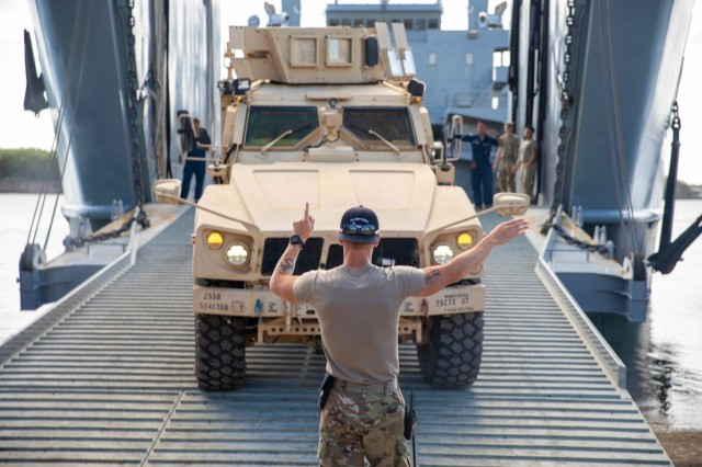 Army Sgt. Seth Rutter guides a vehicle aboard a logistic support vessel in Waipio, Hawaii, Feb. 22, 2021.