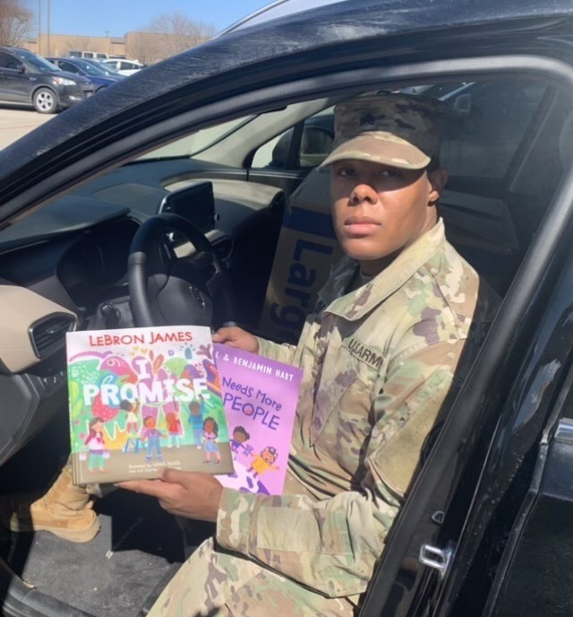 Sgt. Joshua Kirk, Bravo Company, 303rd Military Intelligence Battalion, 504th Military Intelligence Brigade, shows to collected children's books, Feb. 23, 2021, Fort Hood, Texas. Kirk joined the Army in 2017. (U.S. Army photo by Spc. Barry Philson)