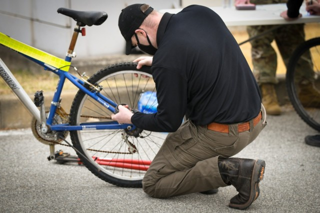 CAMP HUMPHREYS, Republic of Korea - Staff Sgt. Michael Wait, the operations Noncommissioned Officer in Charge for the USAG Humphreys Provost Marshall Office, removes a lock from a previously impounded bike given out during the 2nd Annual Area III USAG Humphreys Religious Support Office (RSO) Community Bicycle Giveaway here, March 6.  During the event, approximately 100 bicycles were which had been previously abandoned or impounded were given out to community members, helping to ensure their effective mobility and transportation. (U.S. Army photo by Spc. Matthew Marcellus)