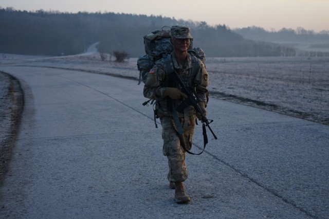 Pfc. Samuil Matveev, USAG Rheinland Pfalz, passes the halfway point during the 10.6 mile ruck march at Oberdachstetten Training Area March 3 as the final event of the Installation Management Command-Europe Best Warrior Competition running from Feb. 28 to Mar. 3. The competition enhances expertise, training, and understanding of the skills needed to be a well-rounded Soldier. Winners will go on to compete at the Installation Management Command level in San Antonio, Texas.