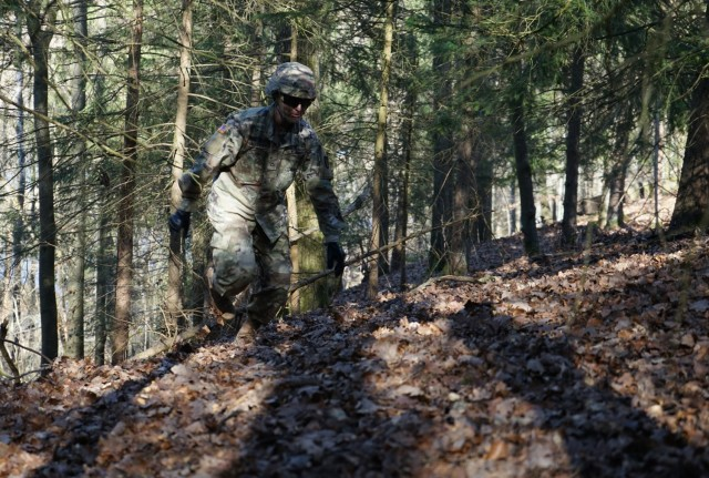 Pfc. Samuil Matveev, USAG Rheinland Pfalz, traverses up a hill during the Rough Terrain Course at Oberdachstetten Training Area March 1 as part of the Installation Management Command-Europe Best Warrior Competition running from Feb. 28 to Mar. 3.  The competition enhances expertise, training, and understanding of the skills needed to be a well-rounded Soldier. Winners will go on to compete at the Installation Management Command level in San Antonio, Texas.