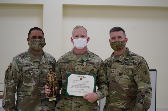 Chief Warrant Officer Two Thomas Downer [Center] receives and Army Commendation Medal from Brig. General Kevin F. Meisler [Right], the commanding general of  the 4th Sustainment Command (Expeditionary), and 1st Sgt. Jorge Pimentel [Left], 4th ESC Headquarter Company First Sergeant.