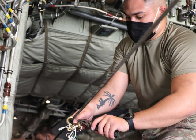 Army Spc. Christian Ramos, 151st Quartermaster Detachment, Fort Bragg, North Carolina, said he is a team leader for air drop system, equipment and repair. The Guam native said once the pallets were loaded onto the aircraft, he and the other riggers used strings and rubber bands to attach the parachutes to the static lines on both the left and right sides of the plane.  (U.S. Army photo by Staff Sgt. Neil McCabe)