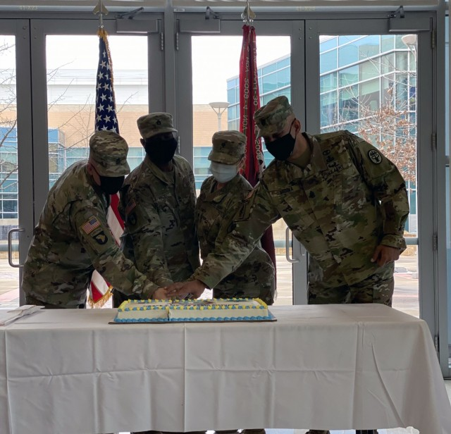 CRDAMC's Senior Enlisted Advisor Command Sgt. Maj. Elvin Medina (right) and Command Sgt. Maj Todd Garner flank the most senior and junior enlisted medical Soldiers in a traditional cake cutting ceremony during the CRDAMC's Army Medical Department Enlisted Corps' 134th Anniversary celebration.