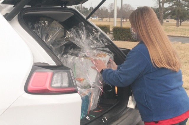 Kelli Hooks, speech pathologist at Andre Lucas Elementary School, loads gift baskets of books into the back of a vehicle March 5 in the school's parking lot. The Prize Patrol Team gifted baskets to 16 winning students as part of the school's Read Across America Week celebration.