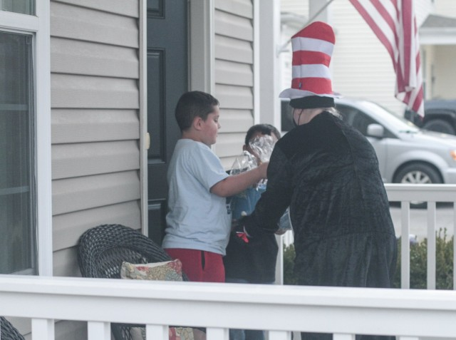Braydon, left, and Hunter Bryant, accept a basket of books from the Cat in the Hat March 5 when the Prize Patrol Team from Andre Lucas Elementary School showed up at their house. Braydon is a third grade student, while his younger brother is in the second grade.
