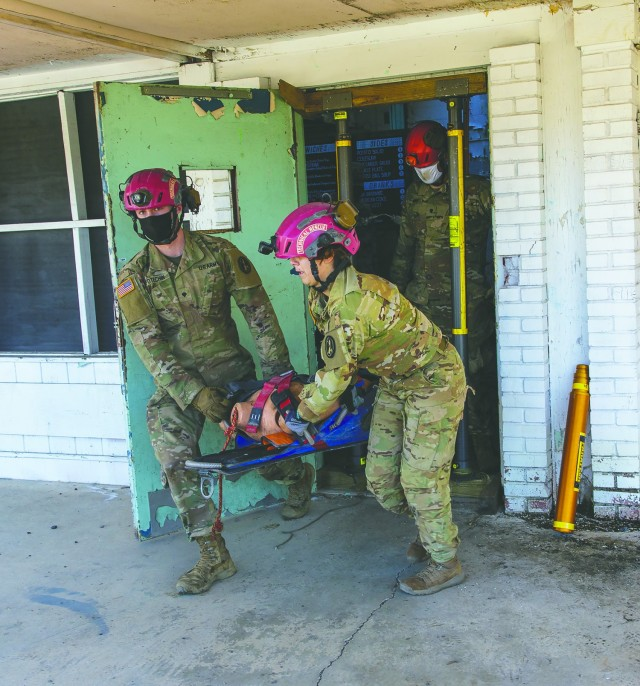Spc. Brendan Potechin, left, and Spc. Vanessa Toro evacuate a helicopter crash victim as the 911th Engineering Techncial Rescue Company holds a competition for Rescuer of the Quarter at the Lorton Training Site, Feb. 25.
