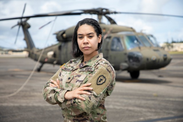 Spc. Kiala Nichols, an aviation operation specialist assigned to 25th Combat Aviation Brigade, 25th Infantry Division at Wheeler Army Airfield, Hawaii, poses for a photo in front of a UH-60 Black Hawk March 4, 2021. Nichols said she has dreams of becoming a Black Hawk pilot.