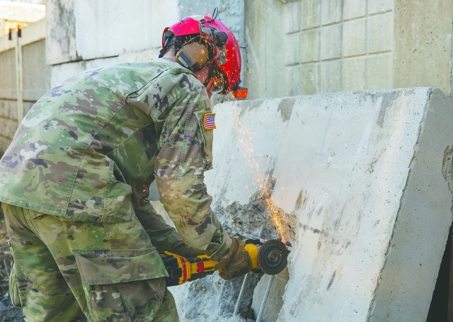 Spec. Jonathan Best, a rescuer wth the 911th Engineering Techncial Rescue Company, cuts rebar to create a hole large enough to climb through, during a competition for Rescuer of the Quarter at the Lorton Training Site, Feb. 25.