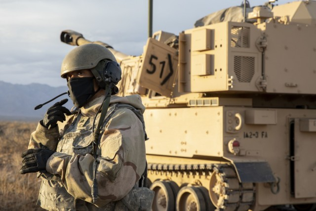 Sgt. Keana Hodgemire, assigned to 2nd Battalion, 3rd Field Artillery Regiment, 1st Brigade Combat Team, 1st Armored Division, stands outside an M-109 Paladin waiting for a fire mission during an artillery qualification training exercise on the Dona Ana Range Complex, New Mexico, March 8. 2021. Hodgemire is the first female noncommissioned officer to hold a Paladin crew member position in the battalion.