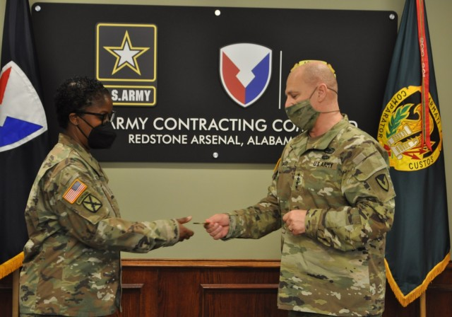 Gen. Daly, Commanding General for U.S. Army Materiel Command, presents an AMC Commanders coin of excellence to Lt. Col. Latia Wickliffe, G-3 Plans Officer for U.S. Army Contracting Command, for her efforts as the action officer for the implementation and coordination of Force Design Update (FDU) Jr. Mar. 9.