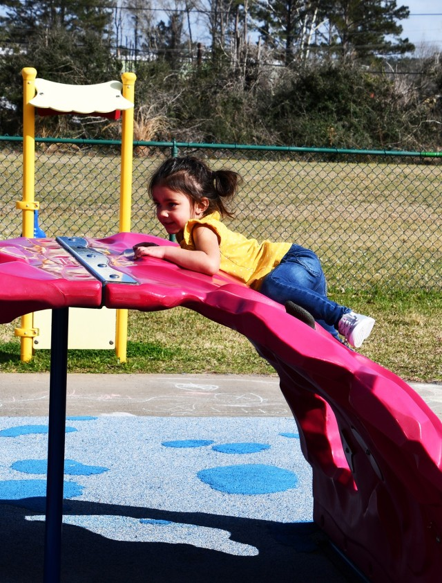 Kayla Morris, 3, works hard to climb on the playground equipment at CDC bldg 3349.