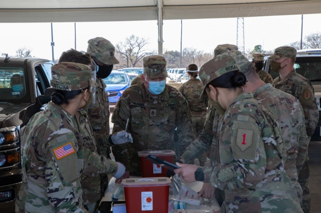 U.S. Army Soldiers with 1st Battalion, 63rd Armored Regiment, 2nd Armor Brigade Combat Team, 1st Infantry Division, prepare COVID vaccine syringes at the Fair Park COVID-19 Community Vaccination Center in Dallas, Texas, Feb. 24, 2021. The Soldiers, deployed from Fort Riley, Kansas, support civilian medical personnel in administering COVID-19 vaccines. U.S. Northern Command, through U.S. Army North, remains committed to providing continued, flexible Department of Defense support to the Federal Emergency Management Agency as part of the whole-of-government response to COVID-19. (U.S. Army photo by Spc. Michael Ybarra, 5th Mobile Public Affairs Detachment)