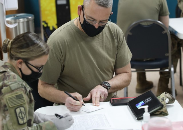 """Army Reserve Command Sgt. Maj. Keith Gwin, deployed to Camp Arifjan, Kuwait, as the senior enlisted advisor to the deputy commanding general of 1st Theater Sustainment Command, reviews his paperwork before receiving the one-dose Janssen Biotech COVID-19 vaccine at the camp's March 13, 2021 rollout of Operation Med Spear. Gwin said, """"Soldiers really need to get onboard to take the vaccine, so we can get back to more normalcy."""" (U.S. Army photo by Staff Sgt. Neil W. McCabe)"""