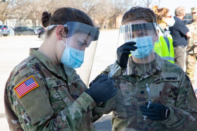 U.S. Army Spc. Haleigh Day (left) and Spc. Zoe Festge (right), 1st Battalion, 63rd Armored Regiment, 2nd Armor Brigade Combat Team, 1st Infantry Division, check the labels on the vaccine syringes at the Fair Park COVID-19 Community Vaccination Center in Dallas, Texas, Feb. 24, 2021. The Soldiers, deployed from Fort Riley, Kansas, support civilian medical personnel in administering COVID-19 vaccines. U.S. Northern Command, through U.S. Army North, remains committed to providing continued, flexible Department of Defense support to the Federal Emergency Management Agency as part of the whole-of-government response to COVID-19. (U.S. Army photo by Spc. Michael Ybarra, 5th Mobile Public Affairs Detachment)