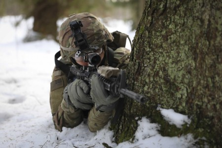 Army Pfc. Dakota Spautz takes cover behind a tree during a combined training exercise with Lithuanian troops at the Kairai Training Area, Lithuania, Feb. 21, 2021.