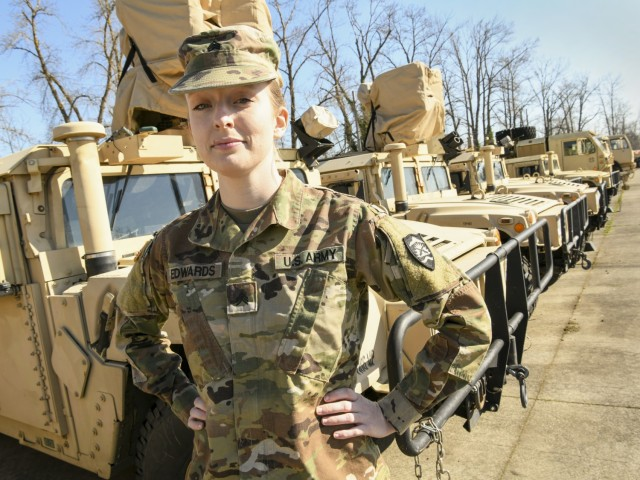Oregon Army National Guard Sgt. Jessica Edwards, an Automated Logistical Specialist pauses for a photo with vehicles assigned to her unit, Salem, Ore., on March 12, 2021. Over the past year, Edwards has been tracking and insuring 821st Troop Command vehicles are properly documented in the Global Combat Support System-Army (GCSS-Army). (National Guard photo by Master Sgt. John Hughel, Oregon Military Department Public Affairs)