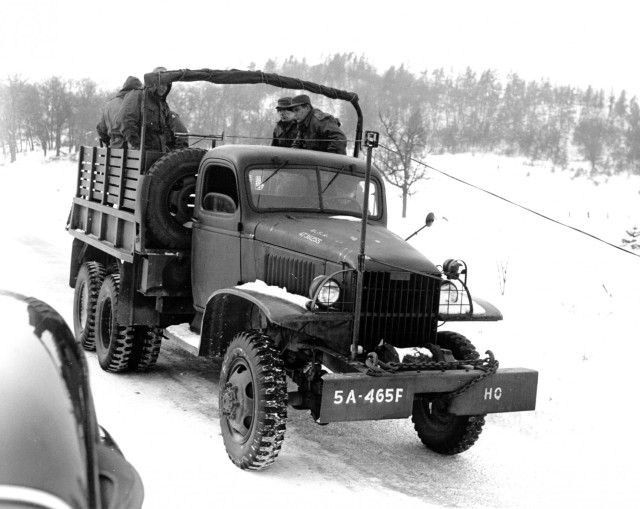 Soldiers demonstrate use of a device attached to 2.5 ton 6x6 truck March 19, 1951, used for picking up W 110 B wire in open terrain at Camp McCoy, Wis.  This device picks up the wire from the side of the road or in open country by lifting it off of the ground through the tension of a power-driven winch on the back of the vehicle. Wire is picked up over the front of the truck, eliminating a loop in the wire  and a wire crew on the ground, giving it a practiced pick-up speed of 10 to 12 miles per hour with an experienced crew.  The device consists of two vertical and horizontal rollers mounted on a rod over the front bumper, and two horizontal rollers in the rear of the cab, enabling the wire to clear the cab.  The pick-up accomplished by a power-driven winch with a clutch.  The device was developed by Sgt. Walter Wehr of Minor, N.D., now with the 465th Field Artillery battalion, Camp McCoy, Wis.  (Historical photo)