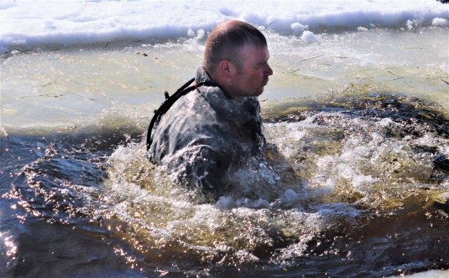 A Fort McCoy Cold-Weather Operations Course (CWOC) Class 21-04 student participates in cold-water immersion training Feb. 26, 2021, at Big Sandy Lake on South Post at Fort McCoy, Wis. CWOC students are trained on a variety of cold-weather subjects, including snowshoe training and skiing as well as how to use ahkio sleds and other gear. Training also focuses on terrain and weather analysis, risk management, cold-weather clothing, developing winter fighting positions in the field, camouflage and concealment, and numerous other areas that are important to know in order to survive and operate in a cold-weather environment. The training is coordinated through the Directorate of Plans, Training, Mobilization and Security at Fort McCoy. (U.S. Army Photo by Scott T. Sturkol, Public Affairs Office, Fort McCoy, Wis.)