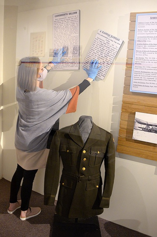 Fayelee Overman, museum technician, arranges enlarged newspaper clippings for display in an aviation exhibit Jan. 27 at the Frontier Army Museum. The recently installed exhibit features the circa 1942 officer's coat that U.S. District Court Judge Arthur Stanley Jr. wore during his service with the U.S. Army Air Corps in World War II. Stanley died in 2001 in Leavenworth at age 99. Photo by Prudence Siebert/Fort Leavenworth Lamp
