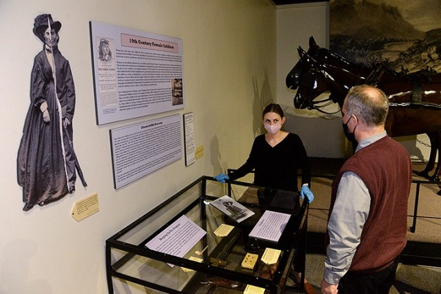 """After arranging information placards and artifacts, Fayelee Overman, museum technician, shows Russell Ronspies, museum curator, the """"19th Century Female Soldiers"""" exhibit for his approval March 11 at the Frontier Army Museum. The exhibit features information about women disguising themselves as men to serve in the military during the Revolutionary, Mexican-America and Civil wars. Photo by Prudence Siebert/Fort Leavenworth Lamp"""