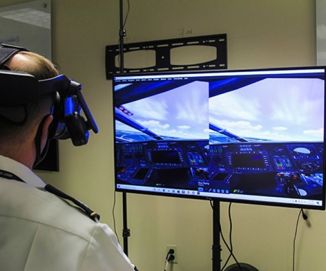 Lt. Col. James Schreiner, an associate professor in the Department of Systems Engineering, demonstrates the latest technological advancements in virtual aviation training while he looks at the screen Tuesday at West Point.