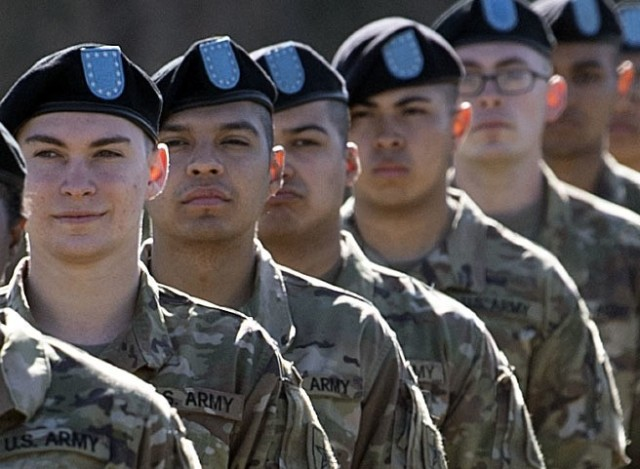 Pvt. Kenny Oliver (second from the left), a trainee with 1st Battalion, 34th Infantry Regiment, stands in formation during his unit's graduation ceremony March 11 at Hilton Field on Fort Jackson. Oliver, who will be going to Advanced Individual Training to be a Religious Affairs Specialist, traded a prestigious music career for Army Greens.